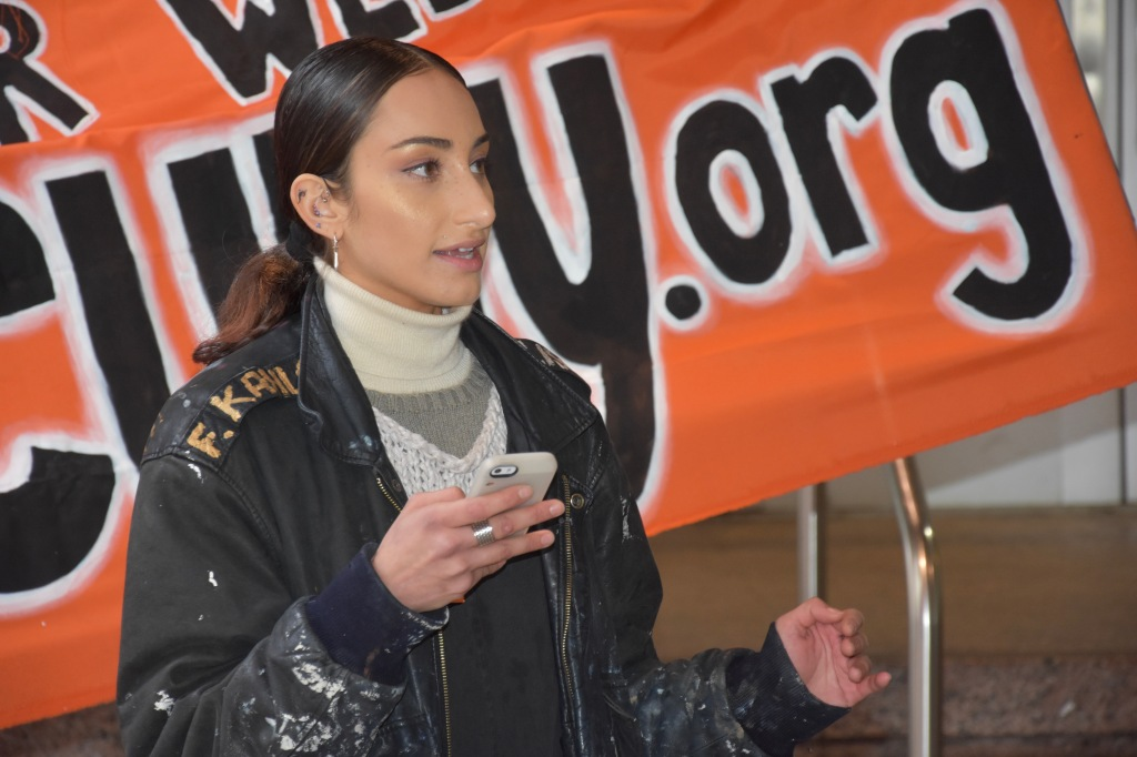 Briana Calderón-Navarro speaking at the anti-Starbucks press conference in front of the Free CUNY banner.