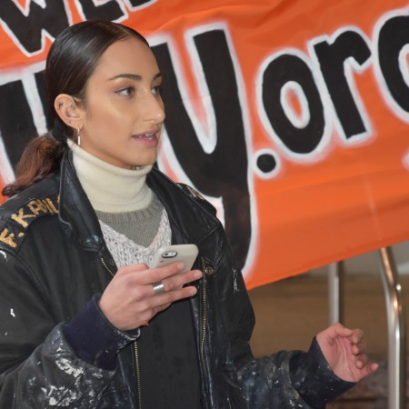 Briana Calderón-Navarro speaks in front of a bright orange Free CUNY banner, holding her phone in her hand.