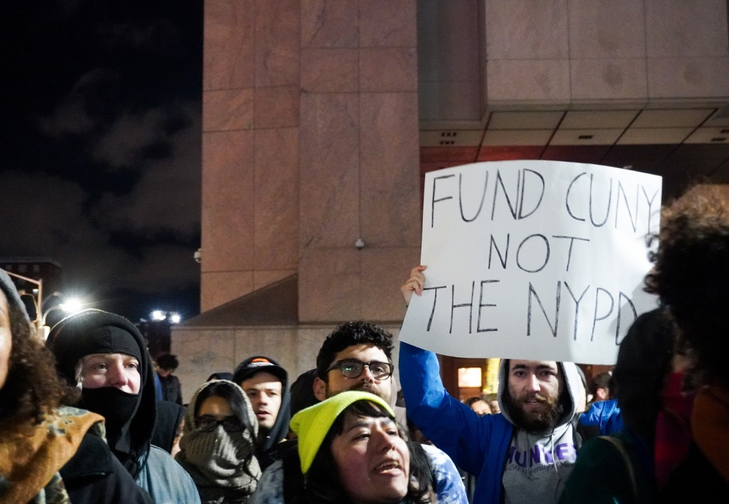 "A protester carries a sign that reads ""FUND CUNY NOT THE NYPD."""